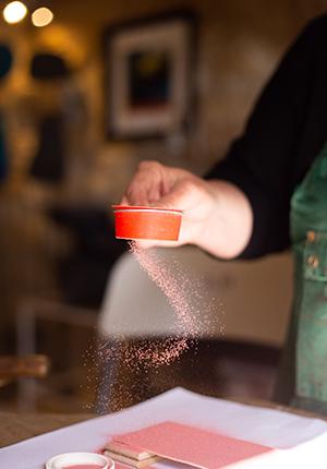 Saupoudrage d'un émail rouge sur du cuivre avant vitrification à 850 degrés