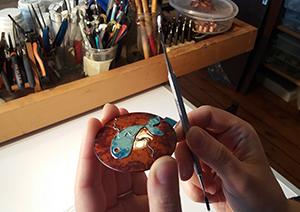 Ateliers découvertes d'émaux sur cuivre de 6 heures pour cette création ronde et unique représentant un poisson bleu sur fond ocre. l atechnique du cloisonné a permis la crétaion de ce motif . le stagiaire a rempli chaque cavité, délimitée par les fils d'argent, avec des émaux de joailliers . L'élève tapote doucement sur le bord de la pièce pour répartir uniformément les émaux déposés avant la vitrification à 850 degrés