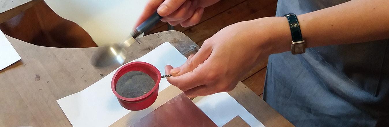 ateliers découvertes 3 heures de l'émaillage sur cuivre - Après avoir déterminé son modèle la stagiaire saupoudre de l'émail à sec sur sa plaque de cuivre