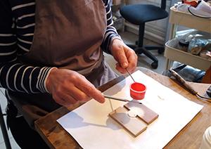 Émaillage d'une pièce de cuivre ronde avec la technique du saupoudrage à sec pour cet atelier découverte de 3 heures.
