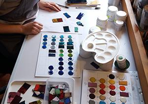 Stagiaire choisissant ses couleurs parmi les échantillons d'émaux colorés opaques et transparents à déposer sur sa pièce en cuivre